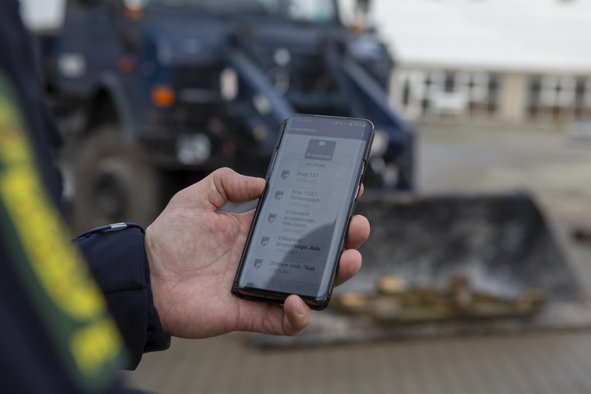 Politimand med mobiltelefon under uroligheder