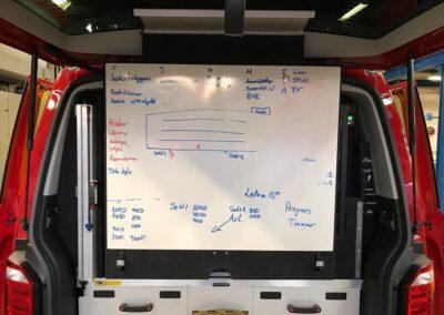 Et whiteboard bagerst i en åben beredsskabsvogn med diverse notater på