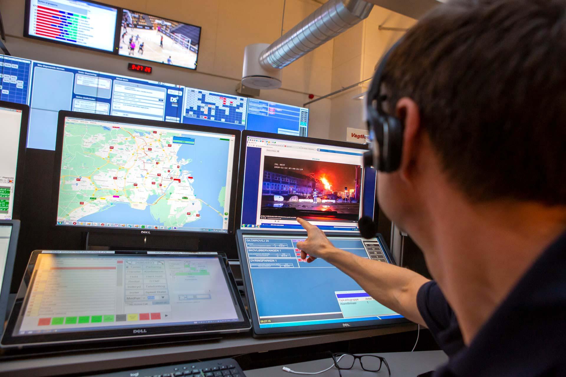 Medarbejder fra Hovedstadens Beredskab interagerer med mange forskellige skærme og systemer